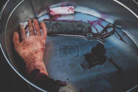 Photo pour Moulage de main de la coupure se trouve dans le sang dans un bassin avec scie médicale pour illustrer le travail des médecins, des chirurgiens en temps de guerre ou de la scène du crime - image libre de droit