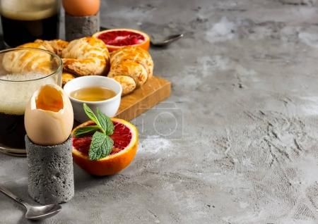 Photo for Breakfast concept with scrambled eggs, a croissant and coffee on a concrete background.Selective focus. Copy space. - Royalty Free Image