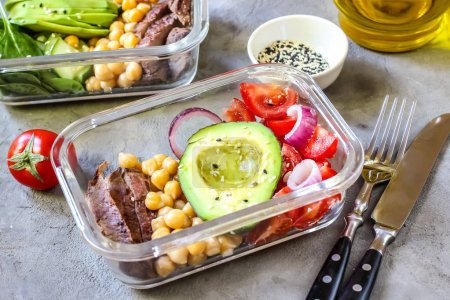 Photo for Healthy meal prep containers with chickpeas, goose meat , tomatoes, avocado, lemon and spinach. Top view - Royalty Free Image