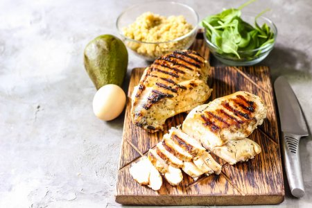 Photo for Grilled chicken fillets on wooden cutting board prep with cooked quinoa and spinach for healthy food - Royalty Free Image