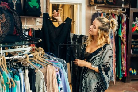The girl chooses clothes in the store