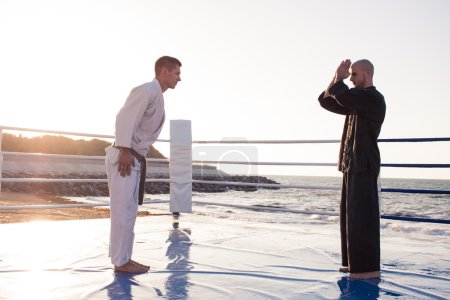 karate fighters are fighting on the beach boxing ring in morning