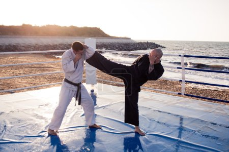Two professional male karate fighters are fighting on the beach boxing ring in morning