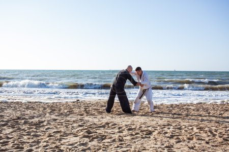 picture of karate sparing on the beach sea background