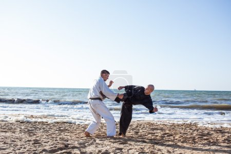 image of karate sparing on the beach sea background