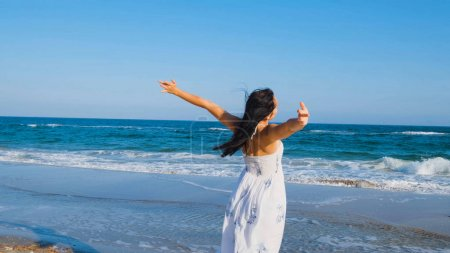 Photo for Young beautiful woman dressed in a white dress walk barefoot on the summer beach - Royalty Free Image