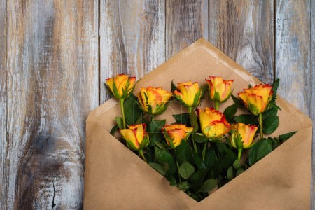 Photo for Flat lay composition with craft paper envelope and roses on wooden table - Royalty Free Image