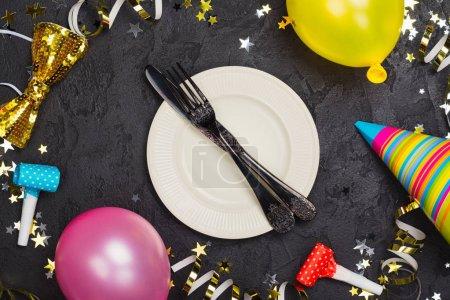 Photo pour Lumineux décor de carnaval de fête avec assiette et couverts sur une table en pierre noire décorée d'accessoires de fête. Espace de copie - image libre de droit