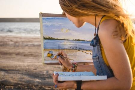 Young woman artist painting landscape in the open air on the beach