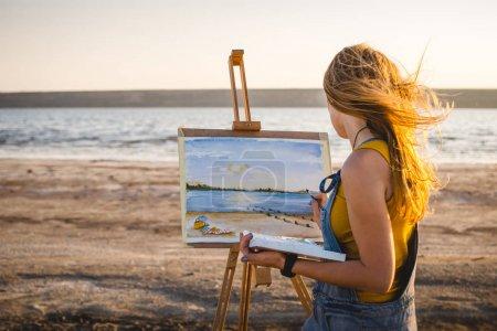 Photo pour Jeune femme artiste peinture paysage en plein air sur la plage - image libre de droit