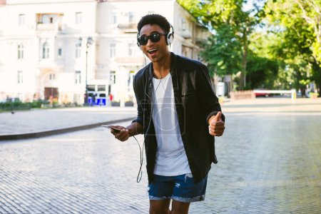 Portrait of young stylish hipster black man in white headphones and sun glasses dancing outdoor in city centre, having some fun