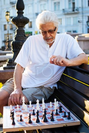 Handsome senior man playing chess
