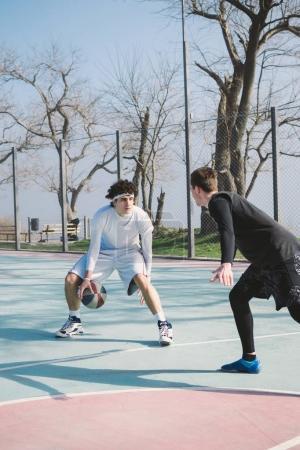 Two basketball player playing basketball outdoors