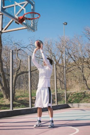 Portrait of a basketball player walking on an outdoor basketball court and dribbling the ball