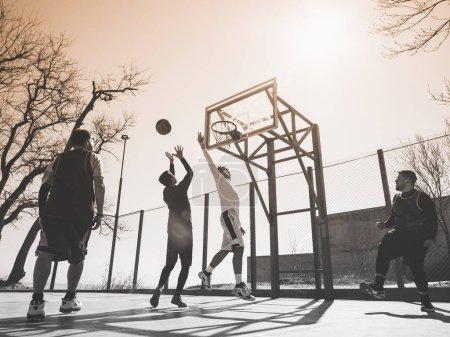 Basketball players playing basketball outdoors