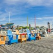 Row of Colourful Adirondack Chairs on a Pier at Su...