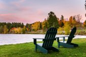 Empty Adirondack Chairs on Grass near the Shore of a Lake at Dusk