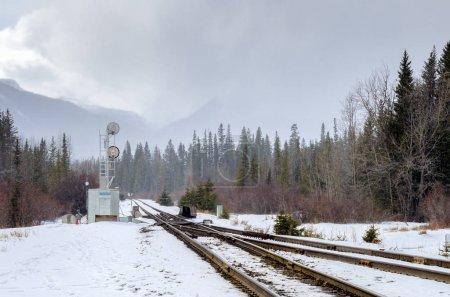 Photo pour Passez le long d'un chemin de fer enneigé à travers un paysage montagneux forestier lors d'une journée d'hiver brumeuse - image libre de droit