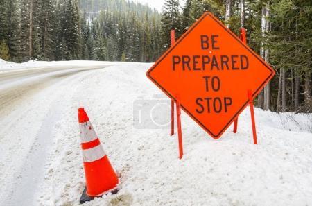 Señal de advertencia naranja al comienzo de un área de mantenimiento a lo largo de una carretera nevada