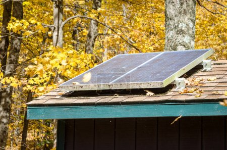 Photo for Solar Panels for Electricity Production on the Roof of a Cabin in the middle of a Wood on a Sunny Autumn Day - Royalty Free Image