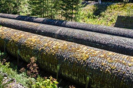 Photo pour Détail de vieux tuyaux d'eau dans une centrale hydroélectrique lors d'une journée d'été ensoleillée - image libre de droit