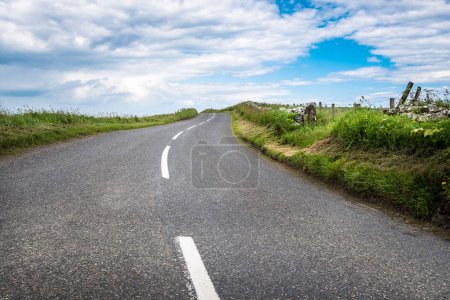 Photo for Empty winding country road and blue sky with clouds. Scotland, UK. - Royalty Free Image