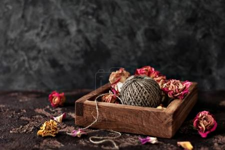 Dried roses and a ball of twine