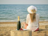 Woman in hat looking at the sunset the sea next to the table with sparkling wine.