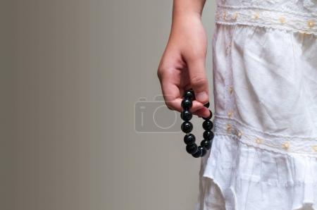 Photo pour Bracelet en perles noires à la main de la fille. Peut être utilisé comme accessoires de mode, aussi comme perles de prière, pour compter les prières ou pratiquer la méditation pleine conscience. Certains pensent que la pierre noire a un pouvoir de protection . - image libre de droit