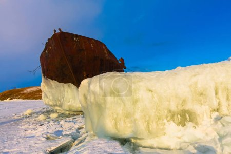 Old rusty ship on ice covered sunset standing on the shore