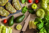 Detoxikační dietu. Zelené smoothie a sanwiches s avokádem. Různé zeleniny na dřevěné pozadí