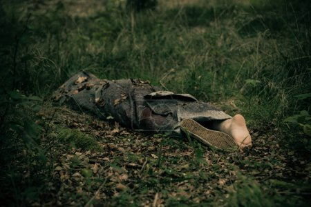 Abandoned body of murder victim lying wrapped in s...