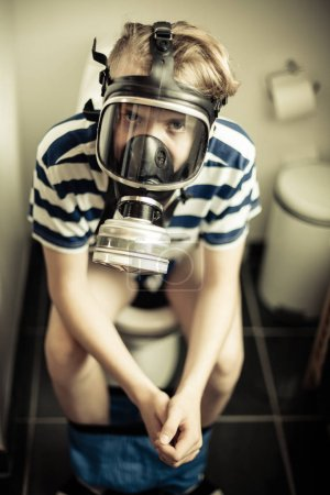 Young boy on toilet wearing gas mask