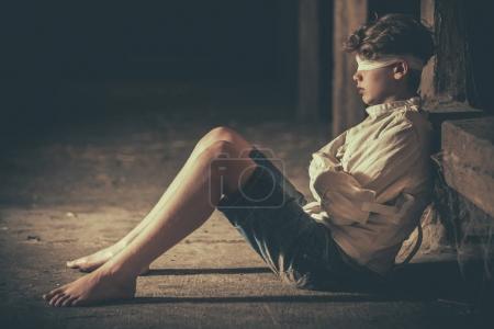 Photo pour Aux tons vintage image d'un adolescent assis pieds nus sur le sol d'un grenier dans un bandeau sur les yeux et le carcan d'une image conceptuelle, vue latérale avec espace copie - image libre de droit