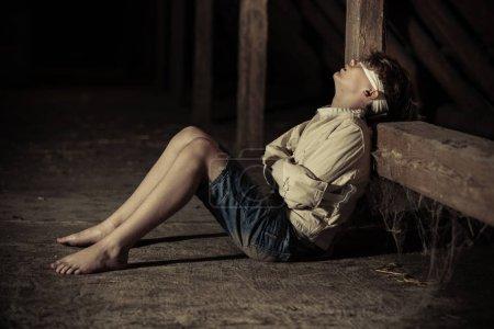 Barefoot teenage boy in captivity