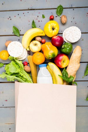 Photo for Grocery shopping concept. Different food in paper bag on wooden background.  Flat lay - Royalty Free Image
