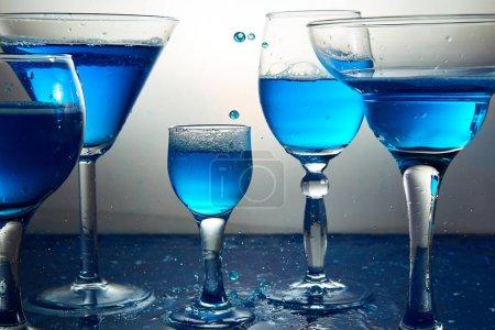 Foto de Muchos vidrios diferentes con azul champagne o alcohol bebida cocteles, copas para martini. Verter. Splash - Imagen libre de derechos