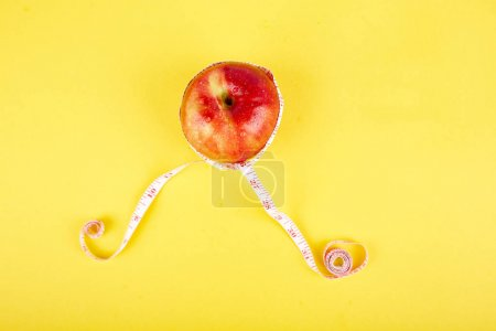 Photo for Measuring tape wrapped around a red apple as a symbol of diet on yellow paper background. Weight loss concept. Diet. Dieting concept. Vegan. Clear food. Healthy. Top view. Minimalism - Royalty Free Image
