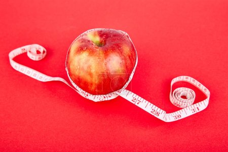 Photo for Measuring tape wrapped around a red apple as a symbol of diet on red paper background. Weight loss concept. Diet. Dieting concept. Vegan. Clear food. Healthy. Top view. Minimalism - Royalty Free Image