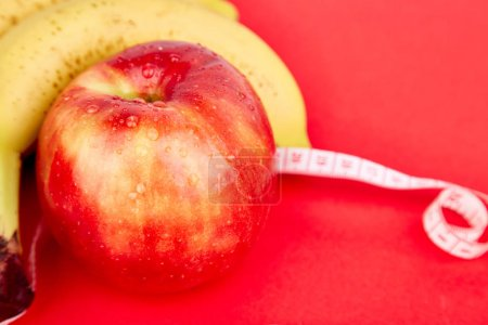 Photo for Measuring tape wrapped around a red apple and banana as a symbol of diet on red paper background. Weight loss concept. Diet. Dieting concept. Vegan. Clear food. Healthy. Top view. Minimalism - Royalty Free Image