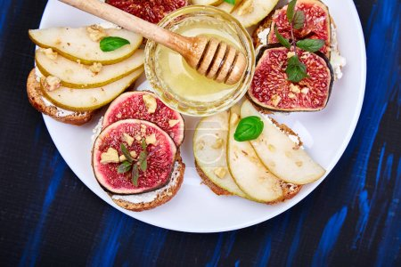 Photo for Bruschetta and Crostini with pear, ricotta cheese, honey, figs, nuts and herbs. Breakfast toasts or snack sandwiches. Antipasto. Italian food. Top view. Copy space. - Royalty Free Image