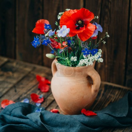 Photo for Wildflowers on a wooden background, a bouquet of poppies, still life - Royalty Free Image