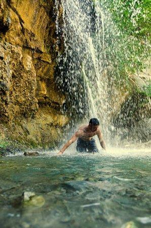 Photo pour Cascade. Jeune homme rafraîchissant dans la cascade . - image libre de droit