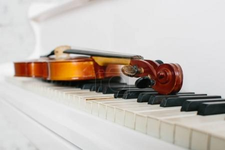 violin and keyboard of white piano