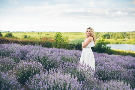 Young and happy blond woman in white dress posing on lavender field near lake