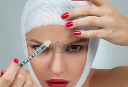 Beautiful woman get injection with bandaged face. Beauty, Fashion and Plastic Surgery concept