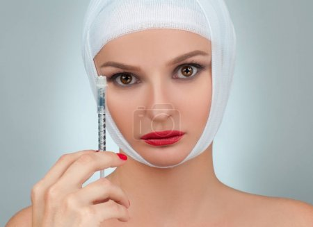 Beautiful woman after plastic surgery with bandaged face. Beauty, Fashion and Plastic Surgery concept