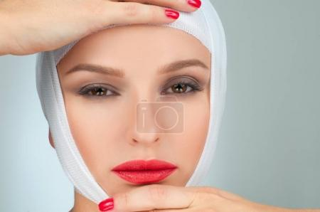 Beautiful woman after plastic surgery with bandaged face. Beauty and Fashion