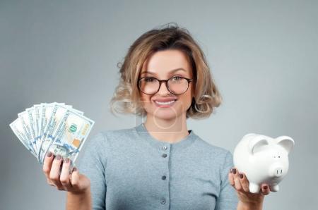 Foto de Mujer sosteniendo alcancía y un montón de billetes de dinero. Ahorro presupuestario financiero, concepto de inversión inteligente - Imagen libre de derechos