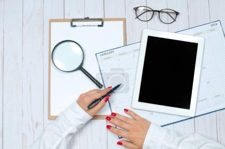 Photo for Top view office desk. Calendar.  Workspace with female hands, clipboard, tablet and glasses - Royalty Free Image